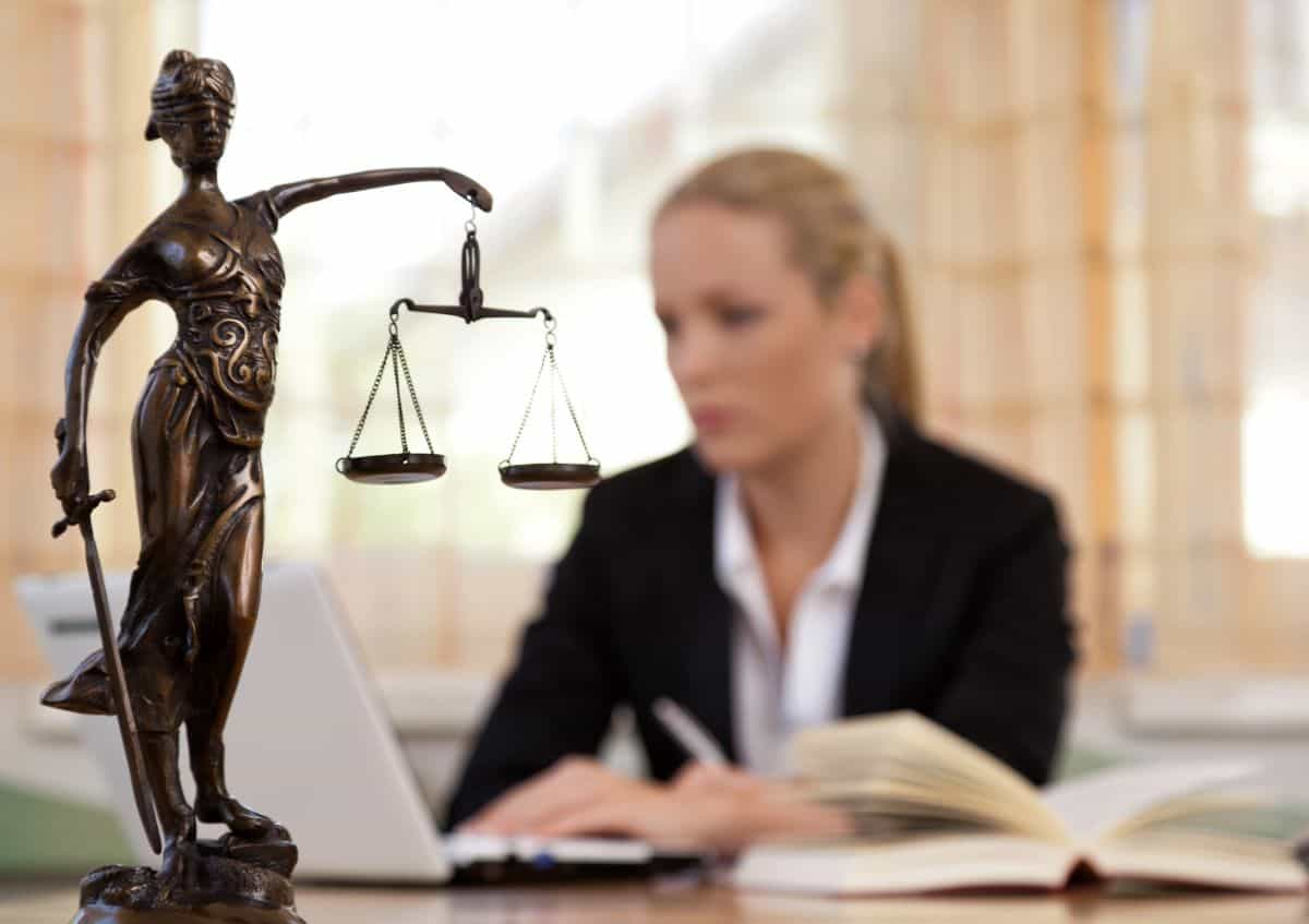 justice statue with lawyer in the background